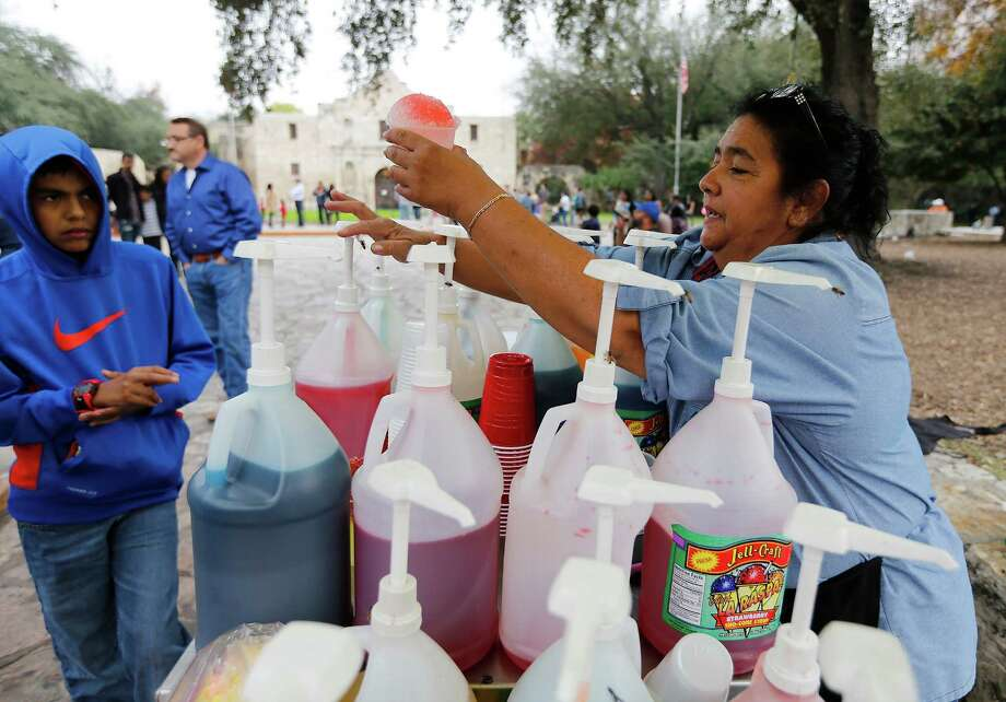 Snow cone vendor Maria Prieto serves a customer in Alamo Plaza. With Christmas Day temperatures in the mid-70s, about 10 degrees higher than typical for Dec. 25, business was brisk. Photo: Kin Man Hui /San Antonio Express-News / ©2015 San Antonio Express-News