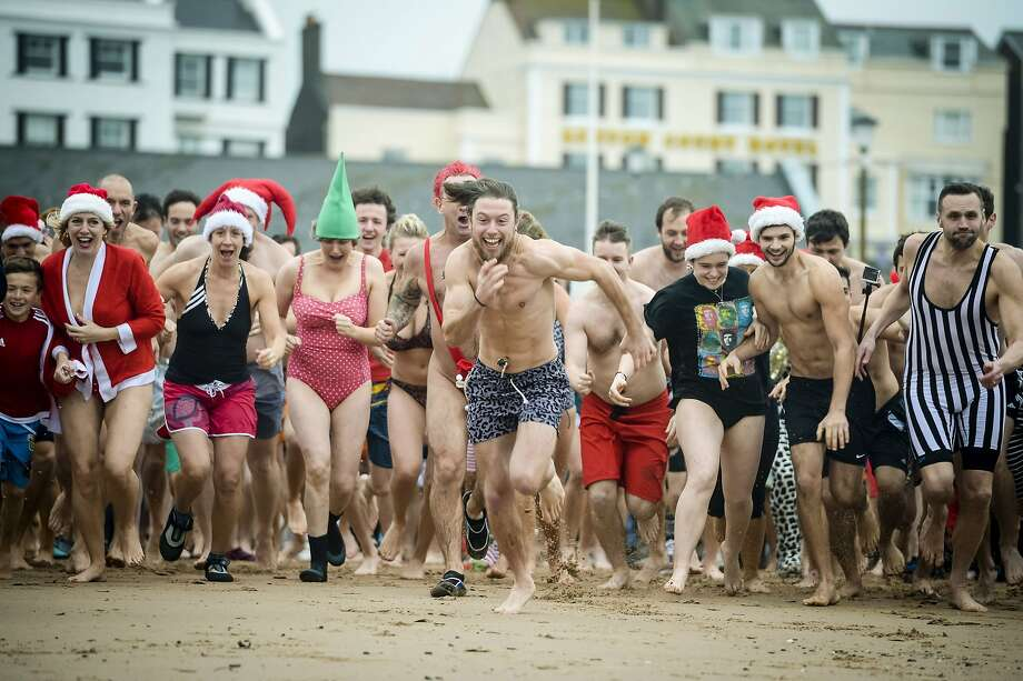 People take part in the annual Exmouth Christmas day swim, at Exmouth beach, in Devon, England, Friday Dec. 25, 2015. Photo: Ben Birchall, Associated Press