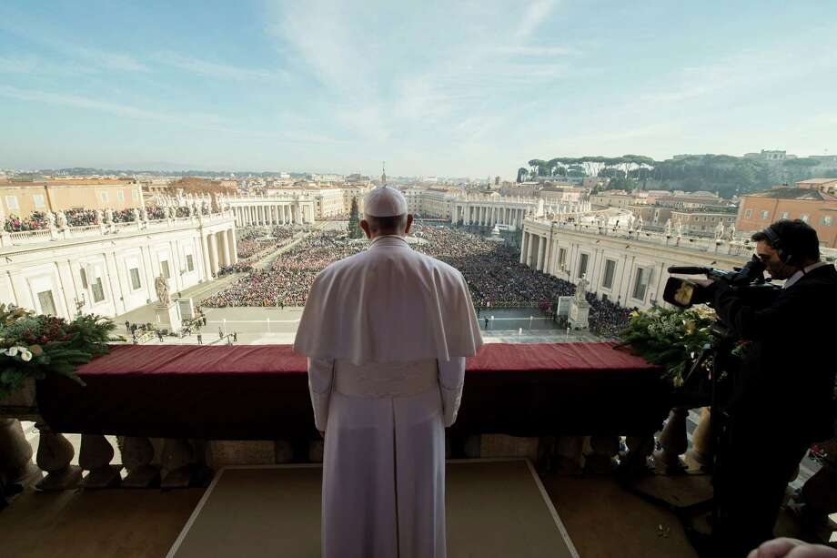 """Pope Francis delivers his """"Urbi et Orbi"""" (to the city and to the world) blessing from the central balcony of St. Peter's Basilica at the Vatican, Friday, Dec. 25, 2015. Pope Francis is praying that recent U.N.-backed peace agreements for Syria and Libya will quickly end the suffering of their people while praising the generosity of those countries that have taken their refugees in. (L'Osservatore Romano/Pool Photo via AP) Photo: POOL / L'Osservatore Romano"""