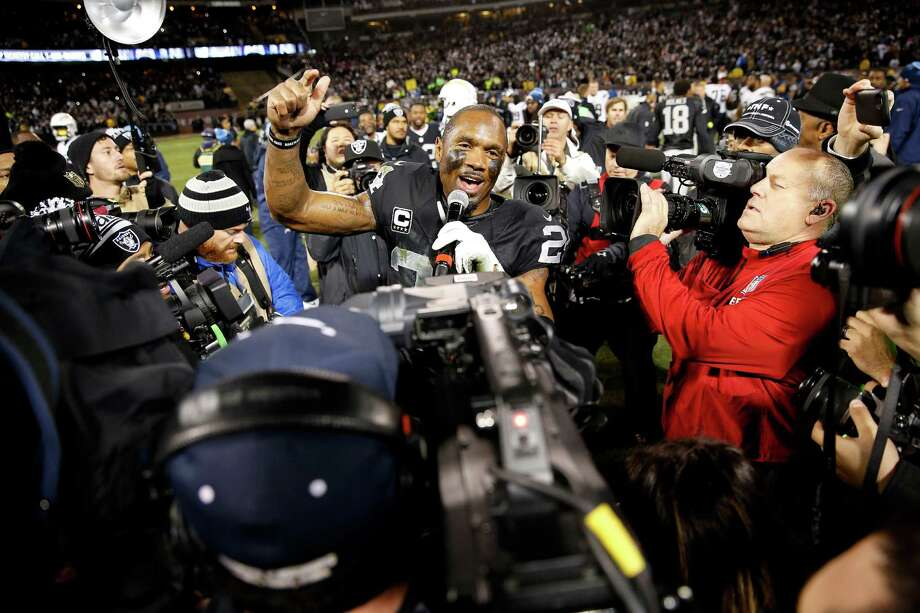 Raiders safety Charles Woodson (24) addresses the Oakland crowd after Thursday night's overtime victory. He is retiring after 18 seasons in the NFL. Photo: Tony Avelar, FRE / FR155217 AP