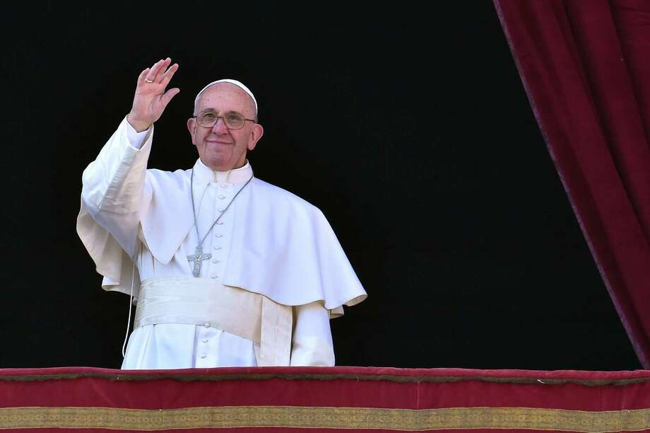 "Pope Francis waves from the balcony of St Peter's Basilica during his ""Urbi et Orbi"" message. Photo: Vincenzo Pinto /Getty Images / AFP"
