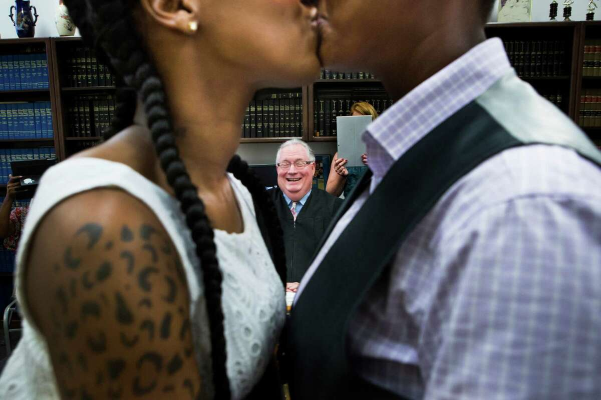 Erikka Givens, left, and Hattie Givens, right, share a kiss after Judge Dale Gorczynski, center, pronounce them wife and wife after a ceremony surrounded by the ladies families and friends. Judge Gorczynski considers marrying couples