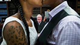 """Erikka Givens, left, and Hattie Givens, right, share a kiss after Judge Dale Gorczynski, center, pronounce them wife and wife after a ceremony surrounded by the ladies families and friends. Judge Gorczynski considers marrying couples """"the happiest part of the job"""". Friday, Aug. 21, 2015, in Houston."""