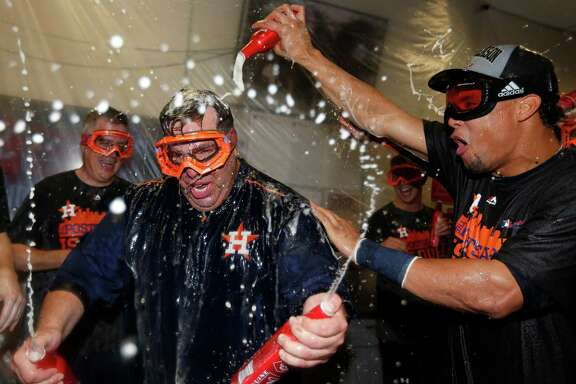 Houston Astros bullpen coach Craig Bjornson gets doused by Carlos Gomez as they celebrate in the locker room after the Astros clinched an American League wild card berth after their game at Chase Field on Sunday, Oct. 4, 2015.