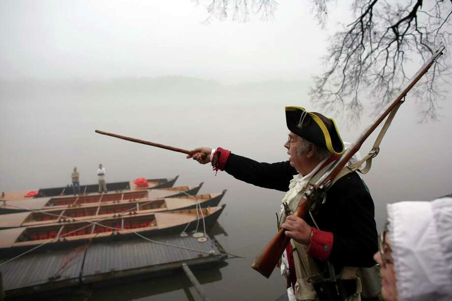 Re-enactor Bill Strunk points across the Delaware River on Friday before the portrayal of Washington's historic crossing that changed the Revolutionary War. Photo: Joseph Kaczmarek / Associated Press / FR109827 AP
