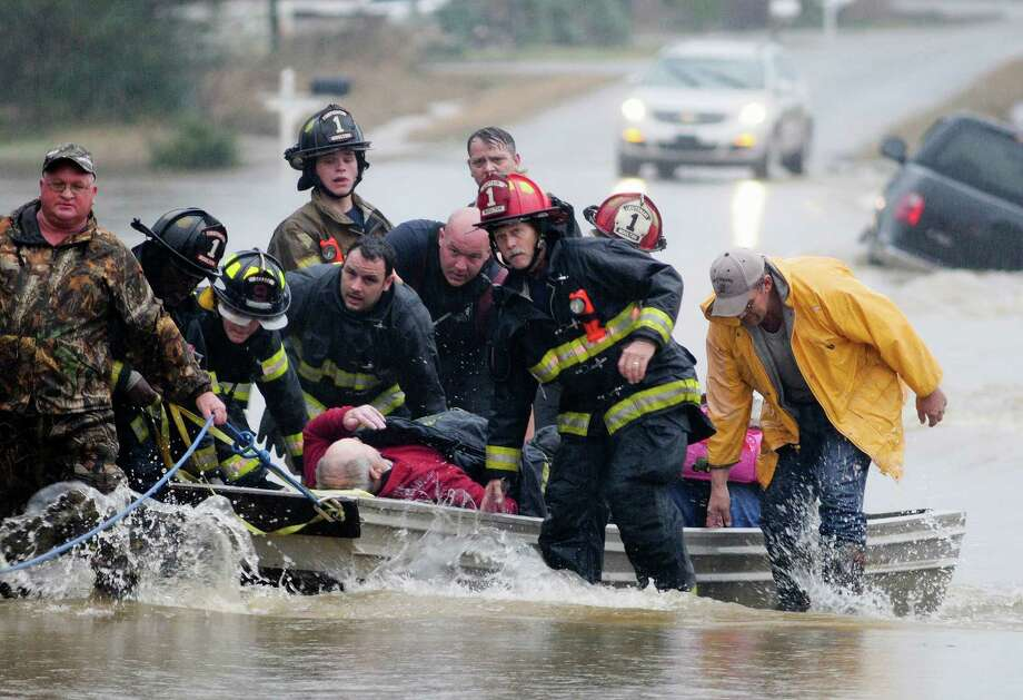 Emergency officials transport James Simmons by boat because water over Byler Road prevented them from reaching him in Moulton, Ala., on Friday. They carried him by boat before loading him into an ambulance. Unseasonably warm weather helped spawn severe storms Friday Photo: Deangelo McDaniel, MBO / AP