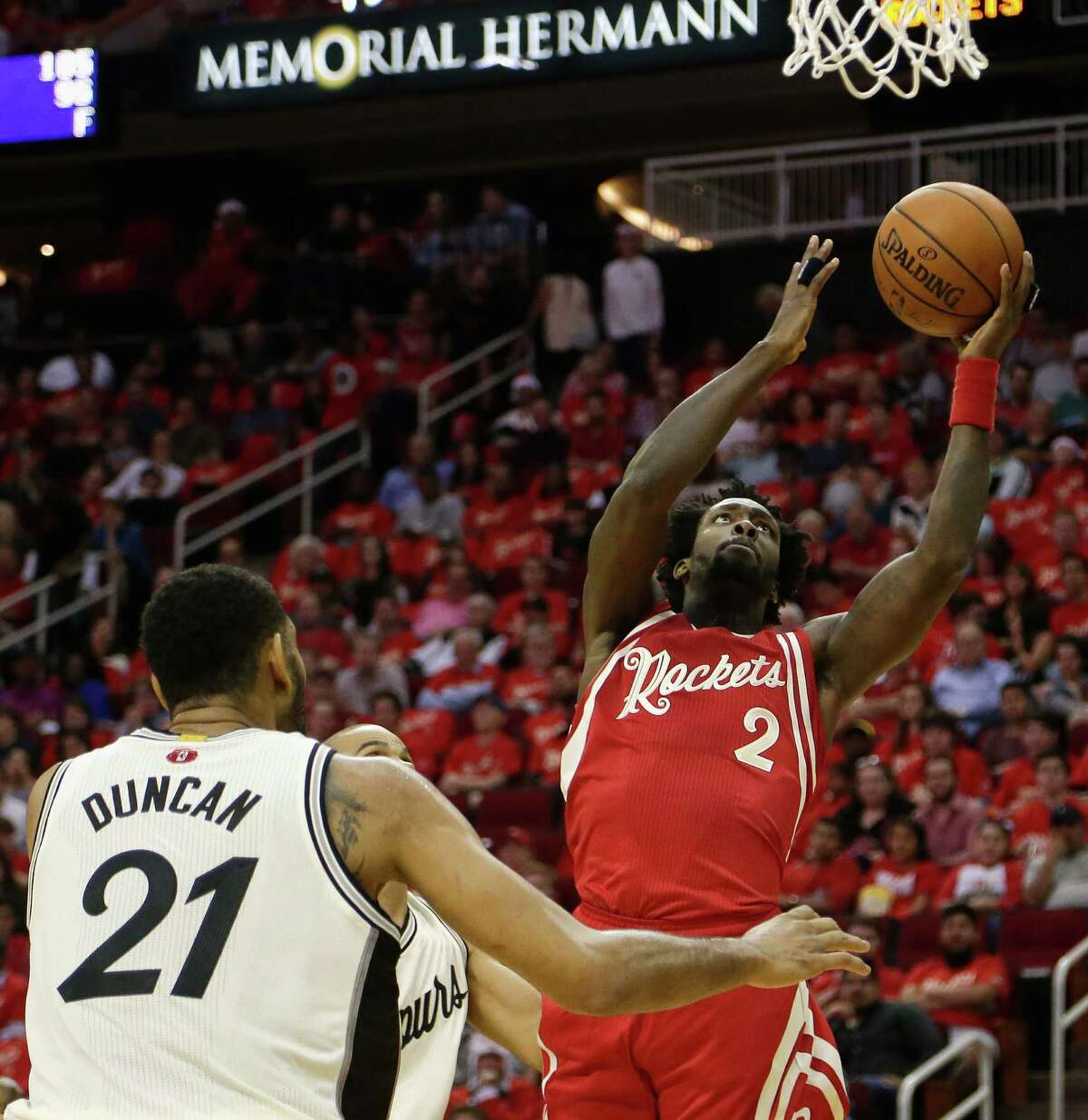 Houston Rockets guard Patrick Beverley (2) drives to the basket against San Antonio Spurs guard Tony Parker, rear, and center Tim Duncan (21) in the first half of an NBA basketball game Friday, Dec. 25, 2015, in Houston. (AP Photo/Bob Levey)