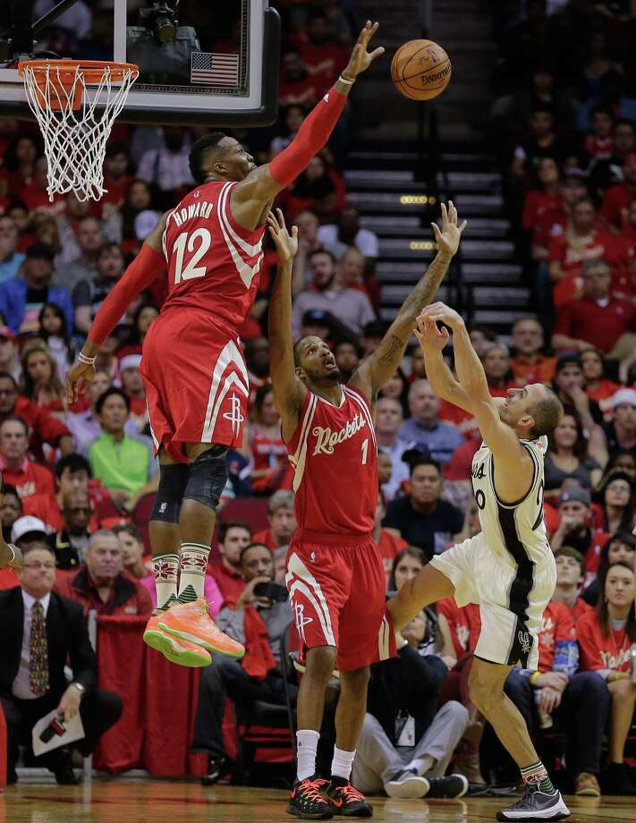 San Antonio Spurs guard Manu Ginobili (20) is fouled by Houston Rockets forward Trevor Ariza (1) as center Dwight Howard (12) blocks his shot attempt in the first half of an NBA basketball game Friday, Dec. 25, 2015, in Houston. (AP Photo/Bob Levey) Photo: Bob Levey, Associated Press / FR156786 AP