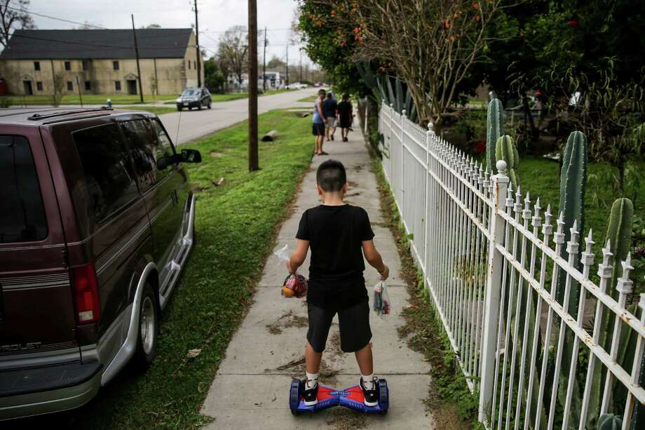 Joseph Dominguez, 11, carries goodie bags from the Latin Fantasy Lowrider Car Club back to his house on his hoverboard, Friday, Dec. 25, 2015. Photo: Michael Ciaglo, Houston Chronicle / © 2015  Houston Chronicle