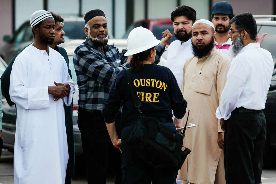 A Houston fire fighter talks to a group of men near the site of a fire at a mosque off Wilcrest Drive Friday, Dec. 25, 2015, in Houston. No one was injured in the blaze, which started around 2:30 p.m., and authorities are still investigating whether or not there was foul play involved. ( Michael Ciaglo / Houston Chronicle ) Photo: Michael Ciaglo, Staff / © 2015  Houston Chronicle