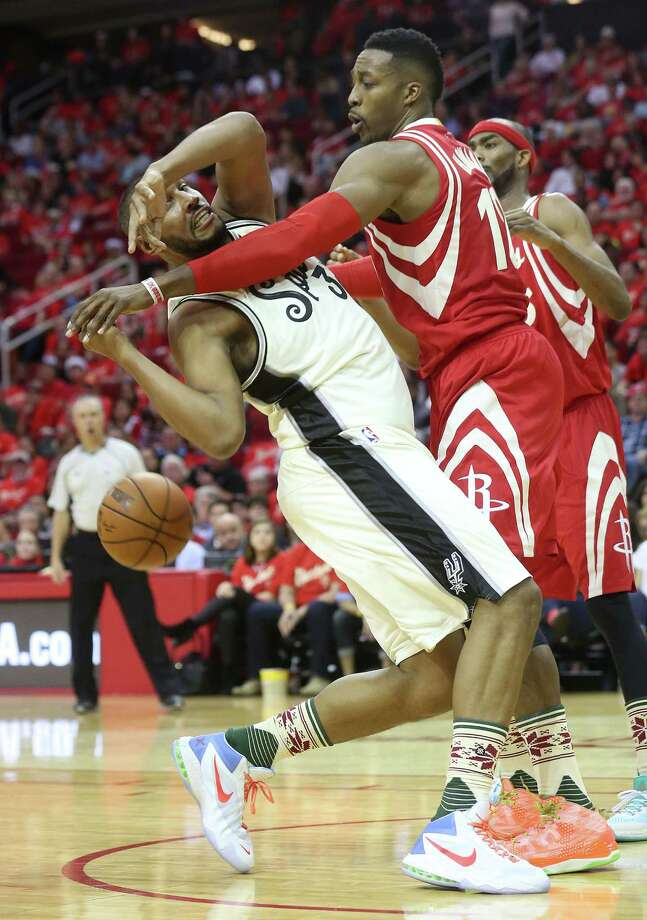 Rockets center Dwight Howard (12) knocks the ball out of the hands of the Spurs' Boris Diaw (33) in the second half. Howard had two steals and 12 rebounds as the Rockets handed the Spurs their sixth loss. Photo: Elizabeth Conley, Staff / © 2015 Houston Chronicle