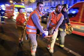 FILE - In this Nov. 13, 2015, file photo, a woman is being evacuated from the Bataclan concert hall after a shooting in Paris. In a poll conducted by the Associated Press and the Times Square Alliance, 64 percent of those polled believe the attacks on Charlie Hebdo and the Jewish market, then the Bataclan concert hall and other city sites, were among the very or extremely important news events of 2015. (AP Photo/Thibault Camus, File)