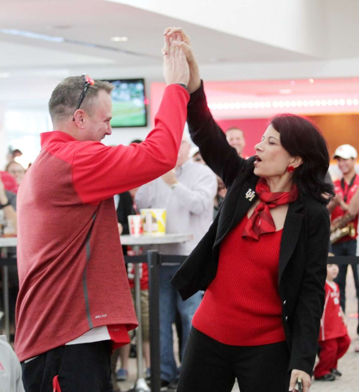 University of Houston system chancellor Renu Khator high fives head football coach Tom Herman at a bowl-selection watch party in the TDECU Stadium club Sunday, Dec. 6, 2015, in Houston. Houston will play Florida State in the Chick-fil-A Peach Bowl on Dec. 31. ( Jon Shapley / Houston Chronicle )