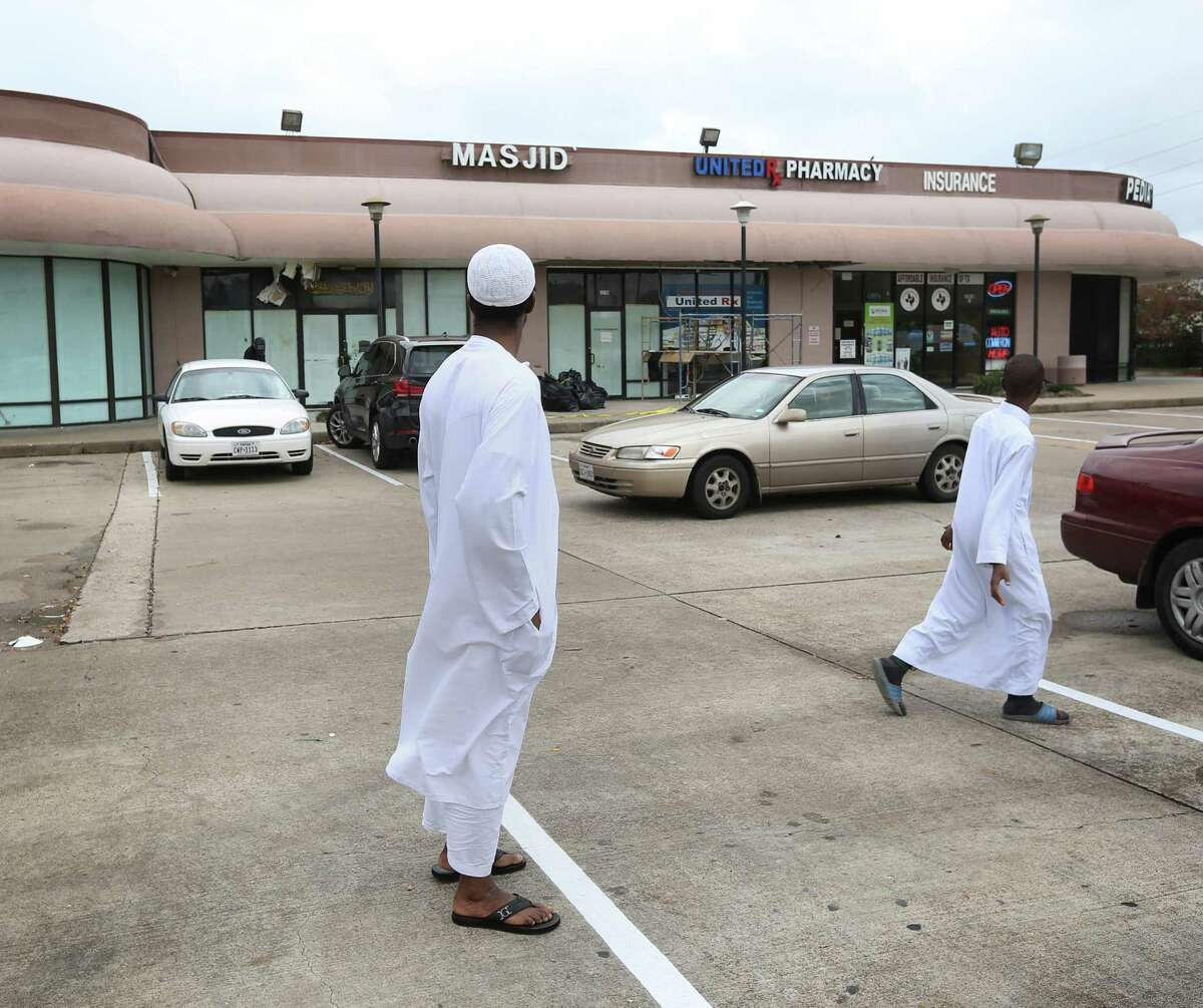 Dramane Diallo, who was responsible for opening the Savoy Mosque each morning, walks to his car after prayers at a temporary location in the shopping center, Saturday, Dec. 26, 2015, in Houston. A two-alarm fire damaged the mosque Christmas day, and authorities are investigating the cause.