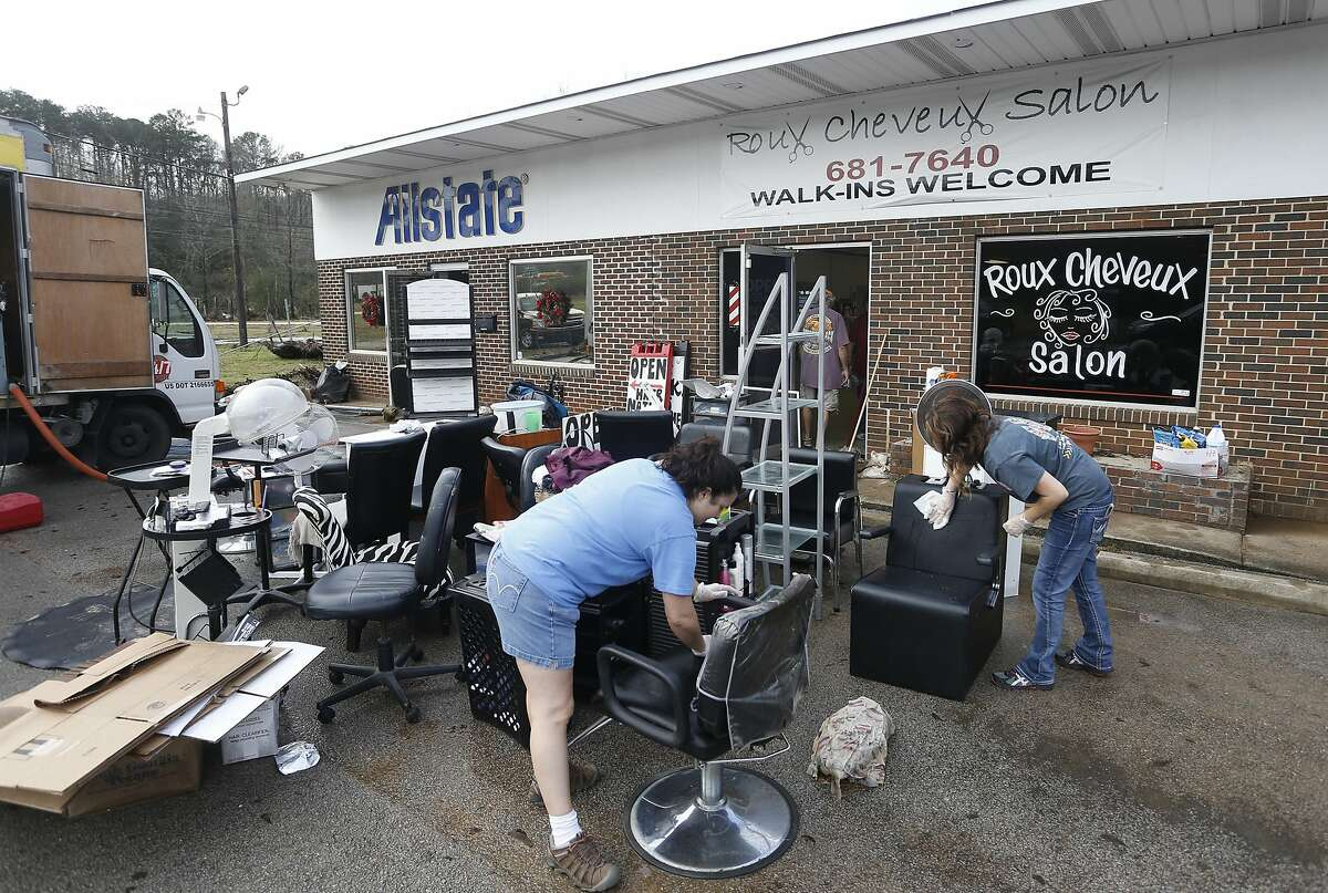 Lena Yawn and Becky Wester clean items from friend Michele Smith's business, Roux Cheveux Salon, Saturday, Dec. 26, 2015, in Pinson, Ala., after floodwaters damaged a row of businesses in this small north Jefferson County town. (AP Photo/ Hal Yeager)
