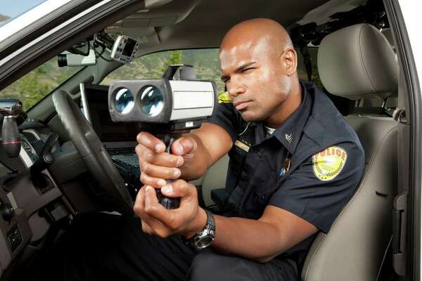 Police Officer checking vehicle speed with radar gun