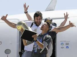 FILE - In this June 17, 2015, file photo, Golden State Warriors guard Stephen Curry, foreground, yells as he carries the Larry O'Brien NBA championship trophy in front of center Andrew Bogut after the team's flight landed in Oakland, Calif. The Warriors defeated the Cleveland Cavaliers to win their first NBA championship since 1975. Curry has been named The Associated Press 2015 Male Athlete of the Year. (AP Photo/Jeff Chiu, File)