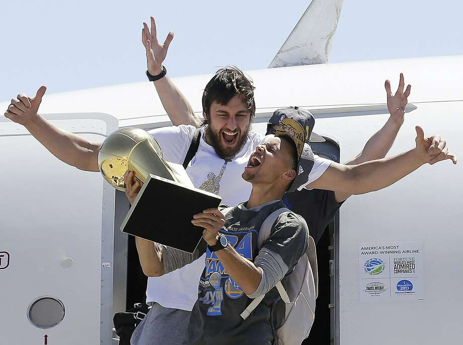 FILE - In this June 17, 2015, file photo, Golden State Warriors guard Stephen Curry, foreground, yells as he carries the Larry O'Brien NBA championship trophy in front of center Andrew Bogut after the team's flight landed in Oakland, Calif. The Warriors defeated the Cleveland Cavaliers to win their first NBA championship since 1975. Curry has been named The Associated Press 2015 Male Athlete of the Year. (AP Photo/Jeff Chiu, File) Photo: Jeff Chiu, Associated Press