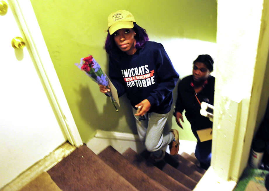 Bridgeport resident Meghan Cooper and two of her friends arrive to bring her a card and some roses at the apartment of Solmarie Rivera on Wood Street in Bridgeport, Conn. on Saturday Dec. 26, 2015. Rivera's son Luis Colon, 14, was killed in a shooting on Christmas Eve day. A Facebook post about Colon's death spread and brought strangers like Cooper to come and show their support. Photo: Christian Abraham / Hearst Connecticut Media / Connecticut Post
