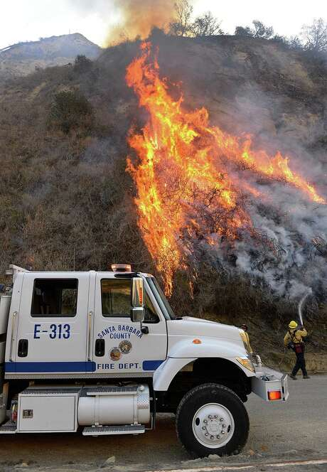 Santa Barbara County firefighter Chris Hansen douses a flare-up on an oil field access road while working a Solimar wildfire in Ventura County.  Saturday, Dec. 26, 2015. The fire, which began on Christmas night, has charred 1,200 acres. (Mike Eliason/Santa Barbara County Fire Dept. via AP) Photo: Mike Eliason, HOGP / Santa Barbara County Fire Dept.