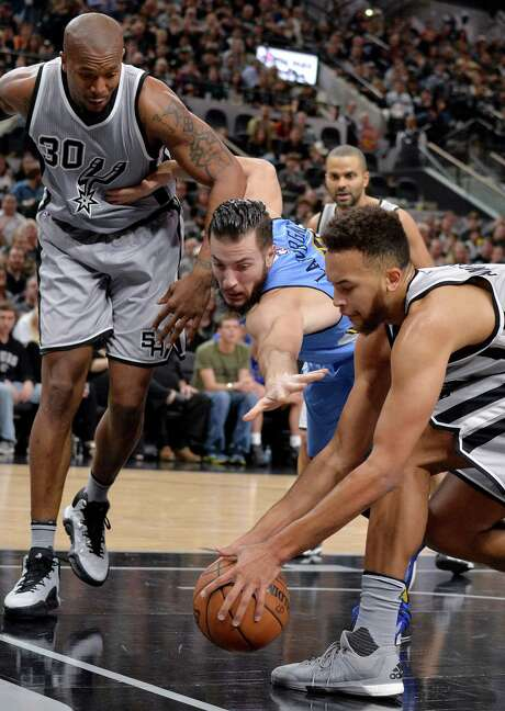 Denver Nuggets forward Joffrey Lauvergne, center, of France, chases the ball against San Antonio Spurs forwards Kyle Anderson, right, and David West during the first half of an NBA basketball game, Saturday, Dec. 26, 2015, in San Antonio. (AP Photo/Darren Abate) Photo: Darren Abate, Associated Press / FR115 AP