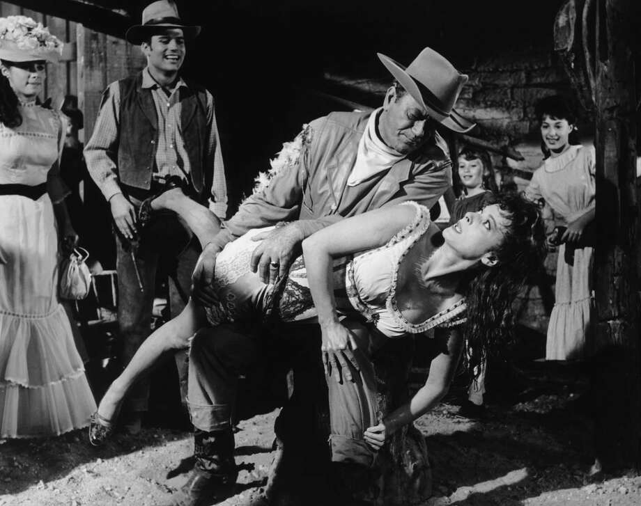 Maureen O'Hara gets a public spanking from John Wayne in the 1963 film, 'McLintock.' Stefanie Powers (left), his on-screen daughter, and Patrick Wayne, his real-life son, watch. Photo: Archive Photos /Getty Images / ONLINE_YES