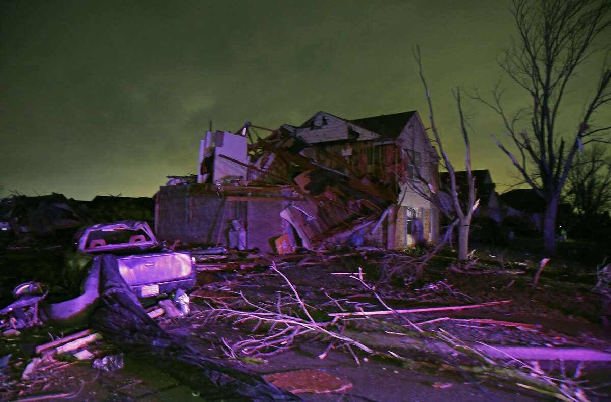 Debris lies on the ground near a home that was heavily damaged by a tornado in Rowlett, Texas, Saturday, Dec. 26, 2015. Tornadoes swept through the Dallas area after dark on Saturday evening causing significant damage.