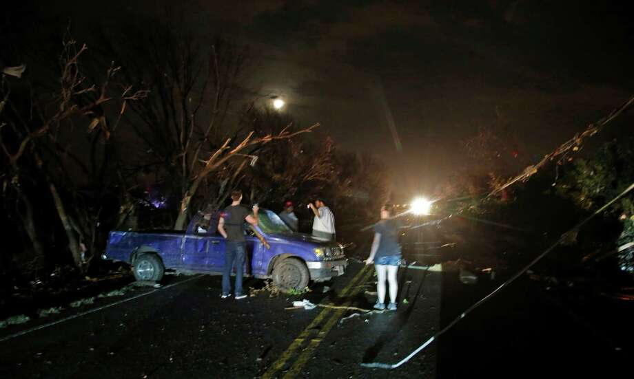 Downed trees and power lines litter the area as neighbors check a damaged pickup looking for the driver after reports of a tornado in Rowlett, Texas, Saturday, Dec. 26, 2015. The driver was later located uninjured. Tornadoes swept through the Dallas area after dark on Saturday evening causing significant damage. (Guy Reynolds/The Dallas Morning News via AP) MANDATORY CREDIT; MAGS OUT; TV OUT; INTERNET USE BY AP MEMBERS ONLY; Photo: Guy Reynolds, AP / The Dallas Morning News
