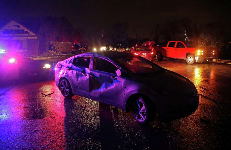 Police car lights illuminate Debbie Spruell's heavily damaged car after a tornado hit in Rowlett, Texas, Saturday, Dec. 26, 2015. Spurell was at home a few blocks away and not in the car at the time and was uninjured according to the The Dallas Morning News. Tornadoes swept through the Dallas area after dark on Saturday evening causing significant damage. (Guy Reynolds/The Dallas Morning News via AP) MANDATORY CREDIT; MAGS OUT; TV OUT; INTERNET USE BY AP MEMBERS ONLY; Photo: Guy Reynolds, AP / The Dallas Morning News