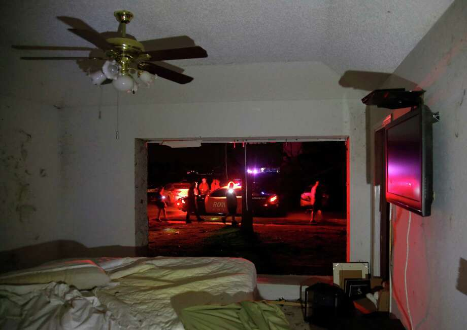Rowlett first responders work in the street across from Daniel O'Connor's heavily damaged home after reports of a tornado in Rowlett, Texas, Saturday, Dec. 26, 2015. The large window in O'Connor's bedroom was completely ripped out and debris blown in. O'Connor was in another room when the tornado struck and was uninjured. (Guy Reynolds/The Dallas Morning News via AP) MANDATORY CREDIT; MAGS OUT; TV OUT; INTERNET USE BY AP MEMBERS ONLY; Photo: Guy Reynolds, AP / The Dallas Morning News