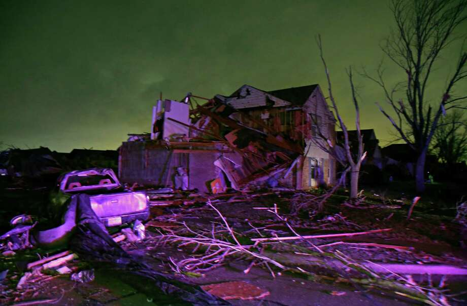 Debris lies on the ground near a home that was heavily damaged by a tornado in Rowlett, Texas, Saturday, Dec. 26, 2015. Tornadoes swept through the Dallas area after dark on Saturday evening causing significant damage. (Guy Reynolds/The Dallas Morning News via AP) MANDATORY CREDIT; MAGS OUT; TV OUT; INTERNET USE BY AP MEMBERS ONLY; NO SALES Photo: Guy Reynolds, MBR / Associated Press / The Dallas Morning News