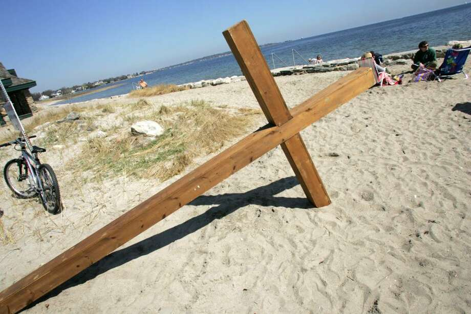 A cross, used for a sunrise service at Greenwich Point on Easter Sunday by the First Congregational Church in Old Greenwich, rests in the sand after being carried to the beach by members of the congregation. Photo: David Ames, David Ames/For Greenwich Time / Greenwich Time