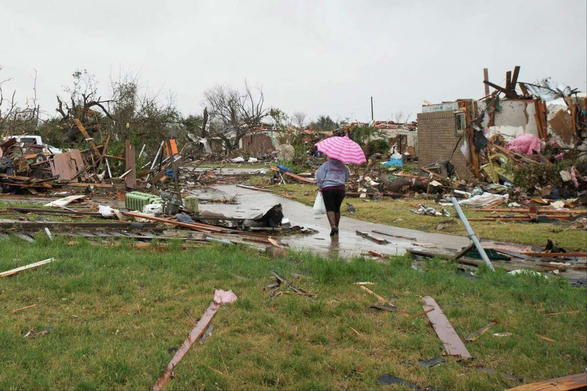 Nery Ceron walks through debris scattered around a neighborhood hit by a tornado the previous evening in Garland, Texas, Dec. 27, 2015. At least 11 people were killed in the Dallas area Saturday night when 11 tornadoes swept North Texas, officials said.
