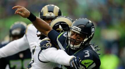 Seattle Seahawks quarterback Russell Wilson (3) is hit by St. Louis Rams' Mark Barron in the first half of an NFL football game, Sunday, Dec. 27, 2015, in Seattle. (AP Photo/John Froschauer)