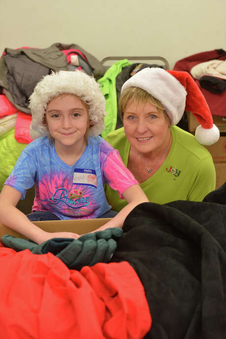 Maya Boone, 9, and her grandmother Joy DeKuck smile prior to a coat give-away for the homeless at First Presbyterian Church. It was Maya's idea to ask for coats as Christmas presents so she could give them away. Photo: Robin Jerstad / San Antonio Express-News