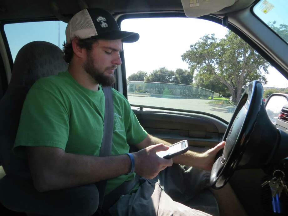 """Landscaper Hunter Ulrich of Schertz prefers using a hand-held phone even though it's prohibited there. """"I don't think it's any more dangerous than opening and closing a bottle of water,"""" he said. Photo by Zeke MacCormack Photo: Zeke MacCormack / San Antonio Express-News"""