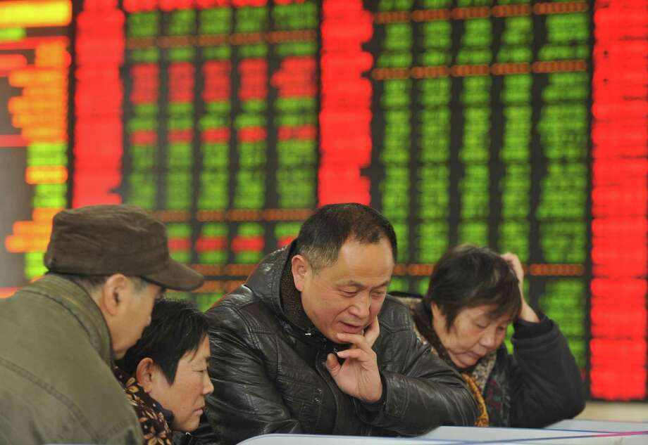 Chinese investors monitor stock prices at a brokerage house in in central China. China's sharp economic slowdown and its surprise decision to devalue its currency squeeze emerging economies, roil financial markets and escalate fears about the global economy was the Associated Press' top business story in 2015. Photo: Associated Press / CHINATOPIX