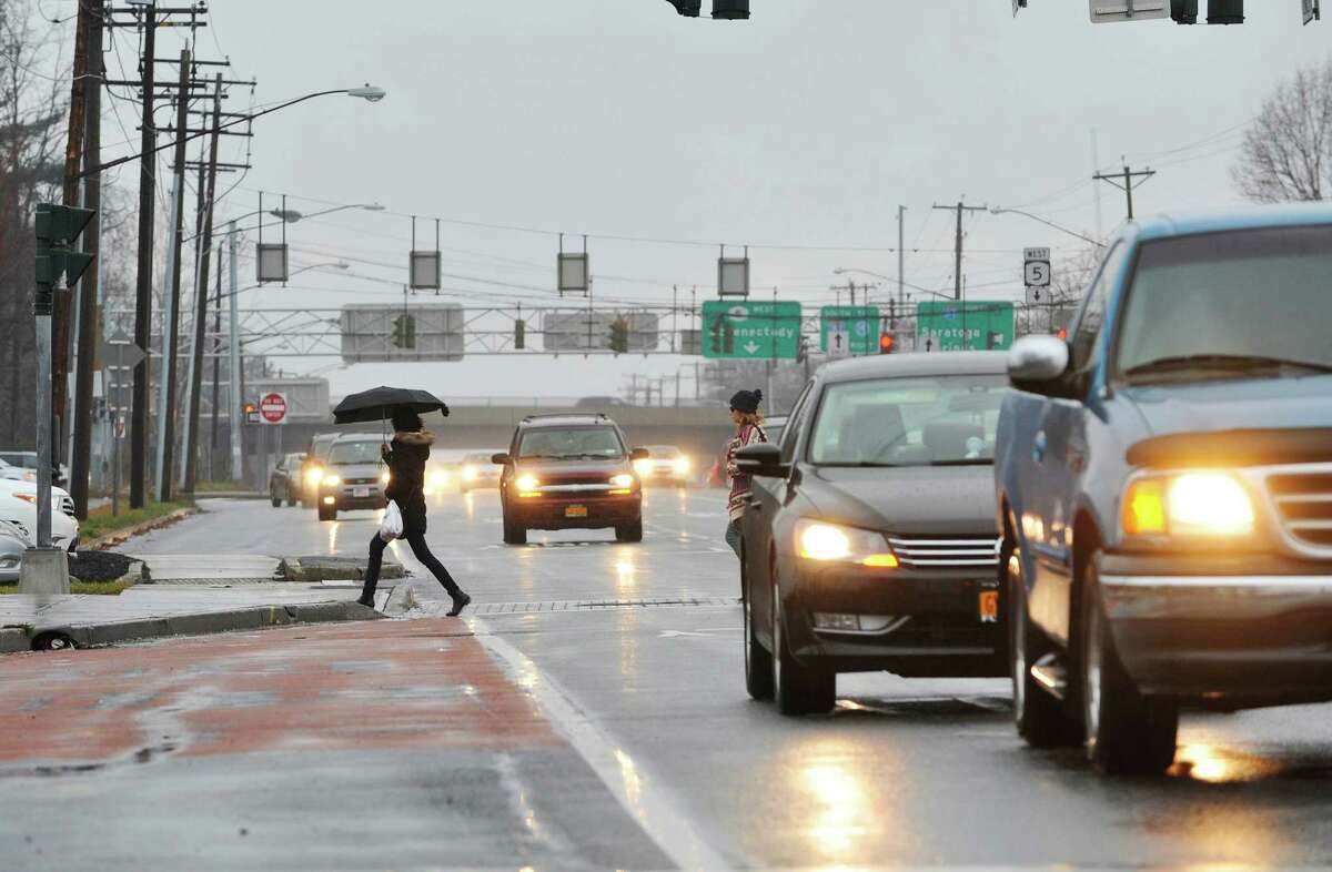 People make their way across Central Ave. in the rain on Sunday, Dec. 27, 2015, in Colonie, N.Y. (Paul Buckowski / Times Union)