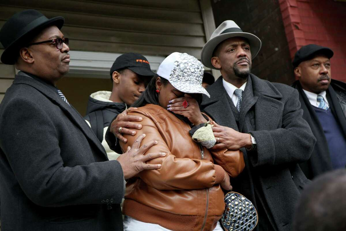 LaTarsha Jones, center, the daughter of Bettie Jones, is comforted by family and friends during a press conference on Sunday, Dec. 27, 2015, in front of the house where Bettie Jones was killed Saturday in the West Garfield Park neighborhood of Chicago. Grieving relatives and friends of two people shot and killed by Chicago police said Sunday that the city's law enforcement officers had failed its residents. (Nancy Stone/Chicago Tribune via AP) MANDATORY CREDIT ORG XMIT: ILCHT101
