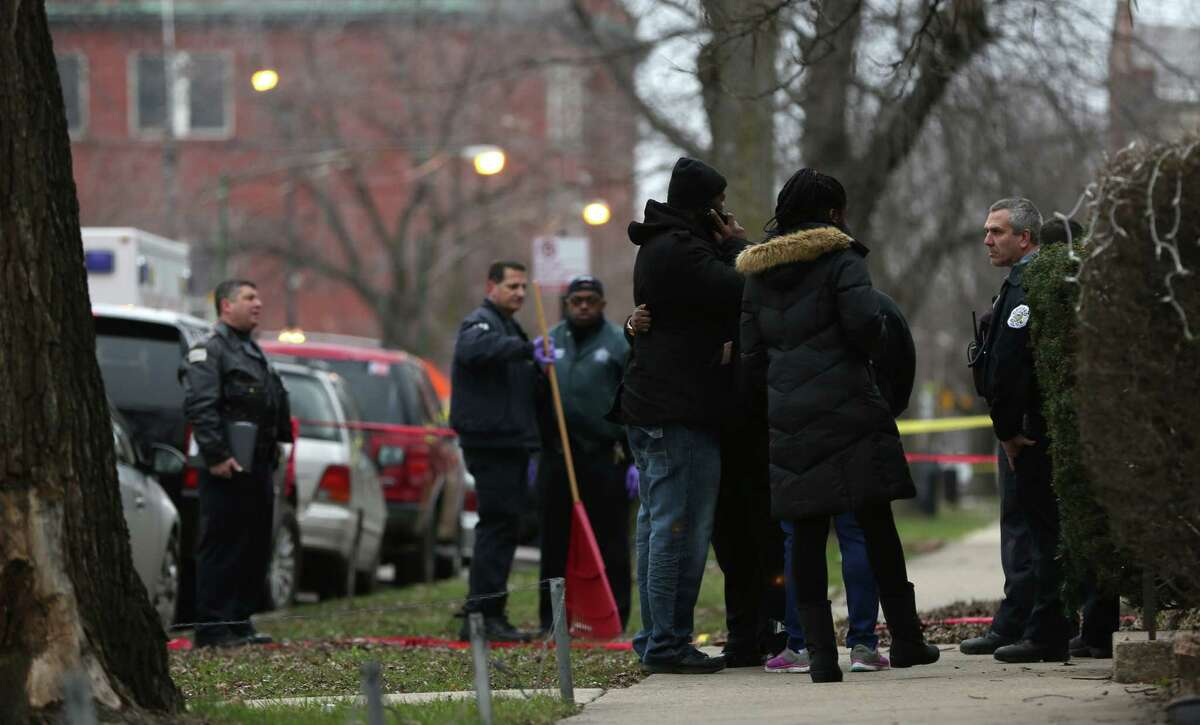 Chicago police officers talk with relatives of one of the two people killed by a police officer, as they investigate a shooting in the entry of their apartment in Chicago on Saturday, Dec. 26, 2015. A Chicago police officer shot and killed two people while responding to a domestic disturbance call in the neighborhood on the city's West Side, police said. (Abel Uribe/Chicago Tribune via AP) ORG XMIT: ILCHT102