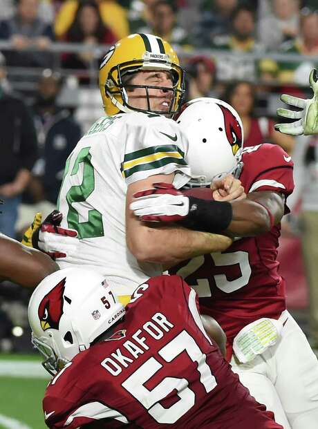 Arizona's Alex Okafor and Jerraud Powers, right, hit Green Bay's Aaron Rodgers, who was sacked eight times. Photo: Norm Hall, Stringer / 2015 Getty Images
