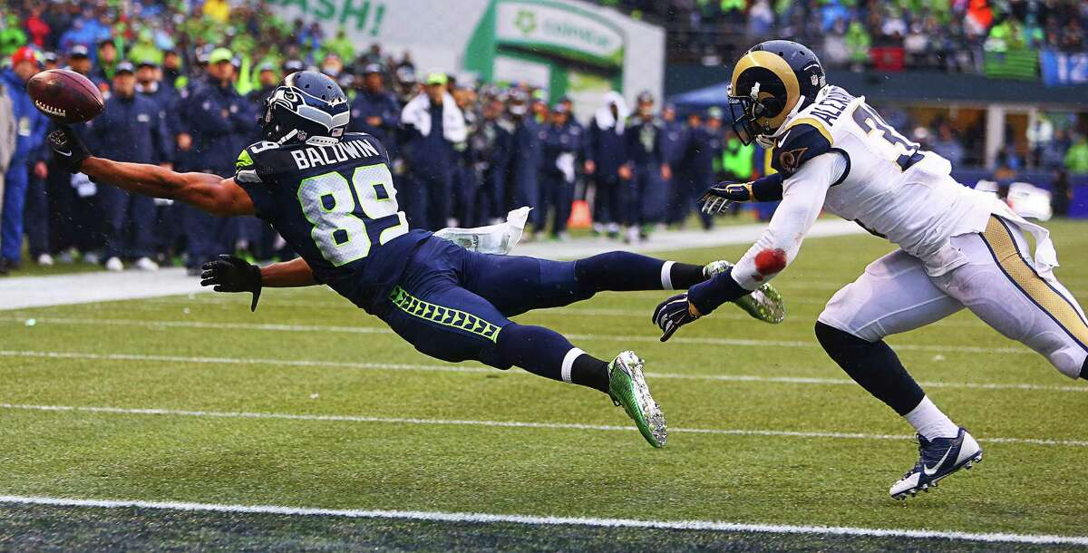 Seahawks wide receiver Doug Baldwin stretches for an out-of-reach pass as Rams safety Maurice Alexander defends during the second quarter of Seattle's game against the St. Louis Rams, Sunday, Dec. 27, 2015 at CenturyLink Field.