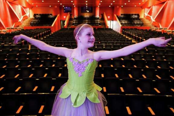 """Peyton Richardson strikes a pose on the Stafford Centre stage before a dress rehearsal of """"The Nutcracker.""""  Peyton, 13, has leukemia, but she has not let her childhood cancer keep her from dancing."""