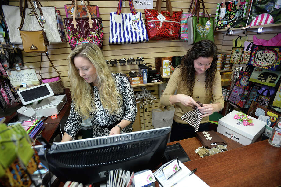 Some area banks and stores are phasing in the technology for their customers to use a new security chip aimed at reducing information theft. Candace Svoboda, left, and Ashley Bell check out a customer at the Ashton House on Wednesday.  