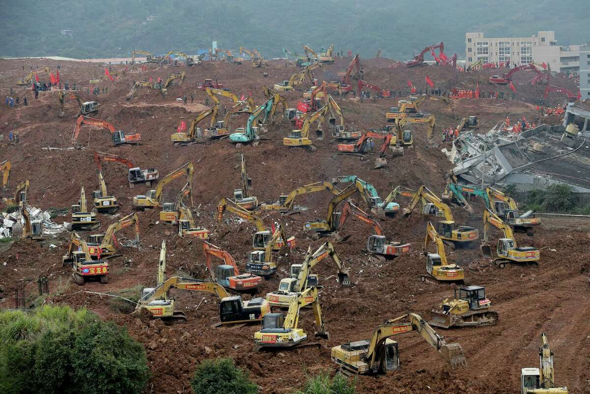 Rescuers use excavators dig the sea of soil to search for potential survivors following a landslide burying buildings at an industrial park in Shenzhen, in south China's Guangdong province, Tuesday, Dec. 22, 2015. A man-made mountain of excavated soil and construction waste crashed into the industrial park on Sunday, Dec. 20.