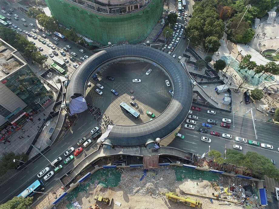 Aerial view of the ring-shaped overpass being demolished on the Heilong River banks on December 27, 2015 in Guiyang, China. The nearly-20-year-old ring-shaped overpass used for people to walk past the streets is to be pulled down and replaced by the underground passages for Guiyang's urban growth. Photo: ChinaFotoPress, Getty Images / 2015 ChinaFotoPress