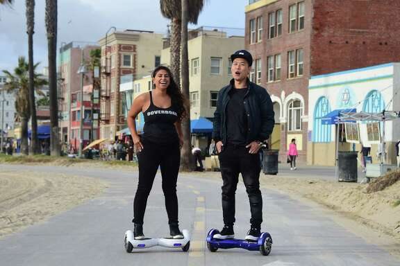 """Michael Tran and Katie Rodriguez use their hoverboards while displaying ease of use on the Venice Beach Boardwalk on December 10, 2015. The hot item on many holiday lists will help you zip around town, the shopping mall and from one end of the workplace to another.These so-called """"hoverboards"""" or self-balancing electric scooters, are surging in popularity in the first season where they have been available at relatively affordable prices -- as low as $300 for some models. AFP PHOTO/ FREDERIC J. BROWNFREDERIC J. BROWN/AFP/Getty Images"""