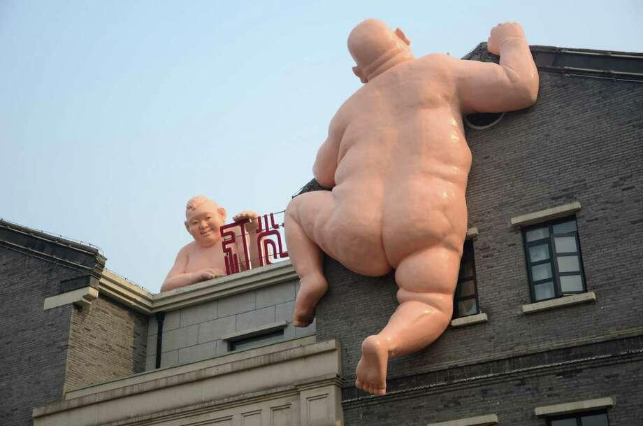 Two giant naked sculptures appear on the side of a restaurant on December 20, 2015 in Jinan, China. There were two naked Buddha statues in the same place last year, but after a short while they were destroyed following a furious online spat. The new pair of sculptures have 'hair'. Photo: ChinaFotoPress, Getty Images / 2015 ChinaFotoPress