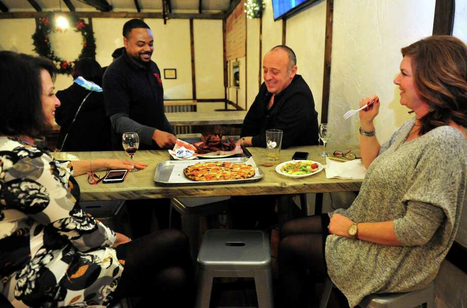 Ricky D. Evans, who owns Ricky D's Rib Shack, brings hot wings to T.H.C. (The Hops Company) owner Umberto Morale, right, at his new business in Derby, Conn. on Wednesday Dec. 16, 2015. At left is Lori Zupardi and at right is Umberto's wife Lisa. Opened for a few weeks now, T.H.C. is located in what was formerly the Grassy Hill Lodge. Zupardi's Apizza, out of West Haven, and Ricky D's Rib Shack, out of New Haven, are set inside T.H.C. to provide the food to patrons. Photo: Christian Abraham / Hearst Connecticut Media / Connecticut Post