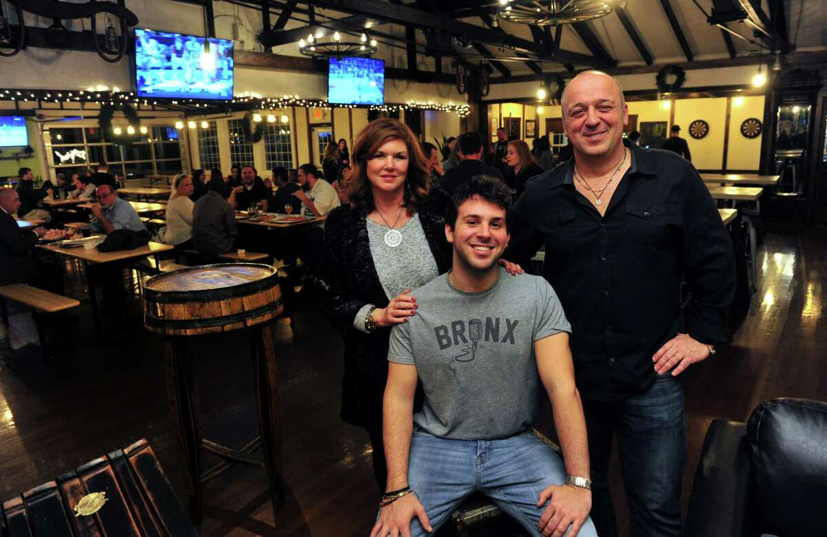 Umberto Morale poses with his wife Lisa and son Giorgio, seated, at his new business T.H.C. (The Hops Company) in Derby, Conn. on Wednesday Dec. 16, 2015. At left is Lori Zupardi and at right is Umberto's wife Lisa. Opened for a few weeks now, T.H.C. was formerly the Grassy Hill Lodge. Zupardi's Apizza, out of West Haven, and Ricky D's Rib Shack, out of New Haven, are set up at T.H.C. to provide the food to patrons.